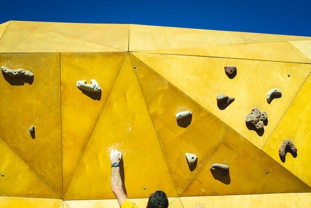 Homme sportif essayant d'atteindre le sommet d'un mur d'escalade avec la force de ses mains et de ses jambes. Photo Premium