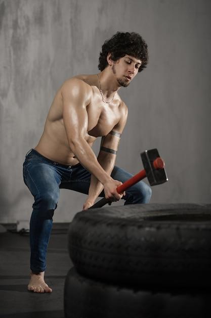 Homme sportif frappe pneu - entraînement au gymnase avec marteau Photo Premium