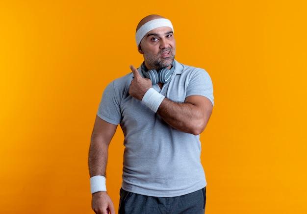 Homme Sportif Mature En Bandeau à L'avant Avec Une Expression Confuse Pointant Vers L'arrière Debout Sur Un Mur Orange Photo gratuit