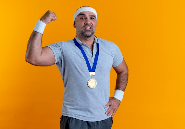 Homme Sportif Mature En Bandeau Avec Médaille D'or Autour De Son Cou Levant Le Poing à La Confiance Debout Sur Le Mur Orange Photo gratuit