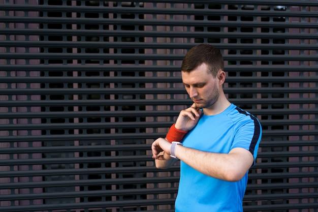 Homme Sportif Vérifie Son Pouls Pendant L'entraînement En Ville Photo gratuit
