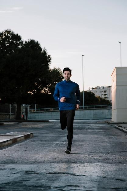 Homme En Sportswear Jogging Sur La Rue Photo gratuit