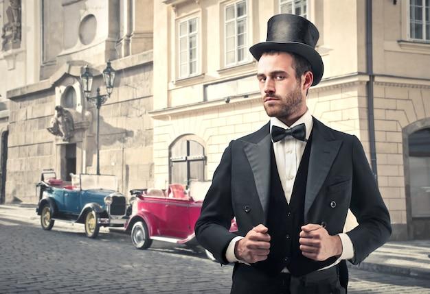 Homme de style vintage avec de vieilles voitures en arrière-plan Photo Premium