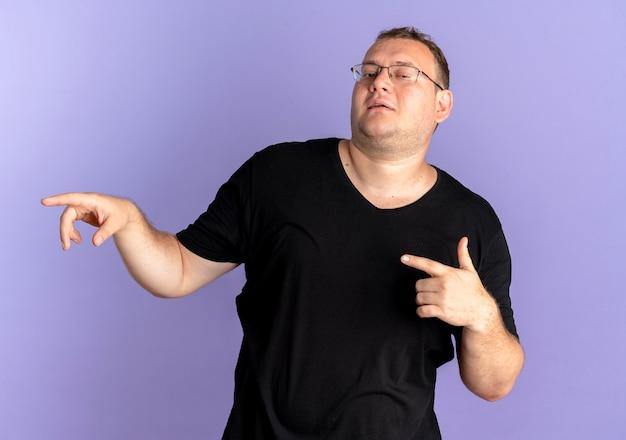 Homme En Surpoids Dans Des Verres Portant Un T-shirt Noir à La Pointe De Confiance Avec L'index Sur Le Côté Sur Bleu Photo gratuit