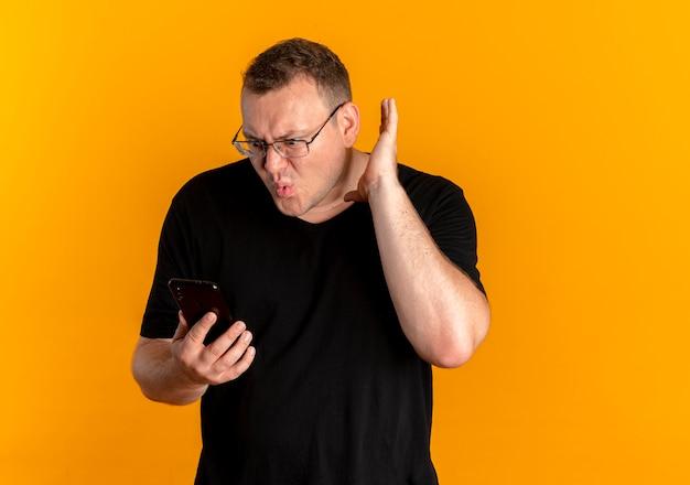 Homme En Surpoids Dans Des Verres Portant Un T-shirt Noir Tenant Le Poing Serrant Le Smartphone Criant Avec Expression De Confusion Debout Sur Un Mur Orange Photo gratuit
