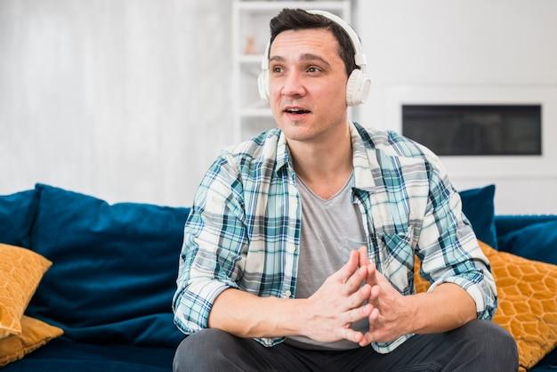 Homme surpris en écoutant de la musique au casque sur un canapé Photo gratuit