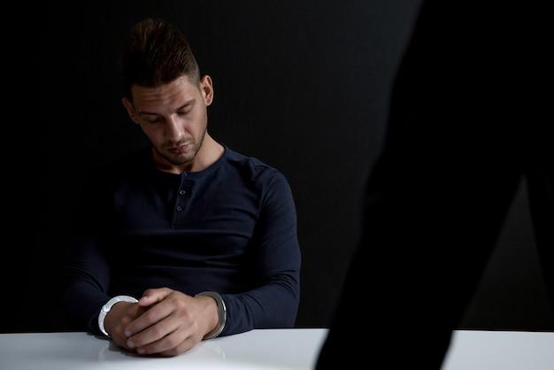 Homme suspect ou criminel avec des menottes dans la salle d'interrogatoire Photo Premium