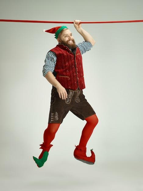 Homme Sympathique Habillé Comme Un Drôle De Gnome Posant Sur Un Gris Isolé Photo gratuit