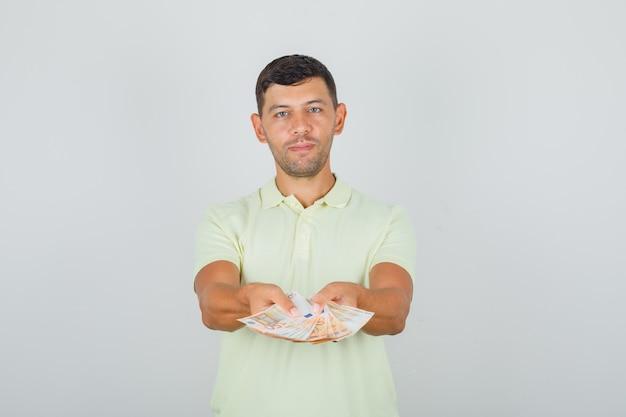 Homme En T-shirt Jaune Tenant Des Billets En Euros Photo gratuit
