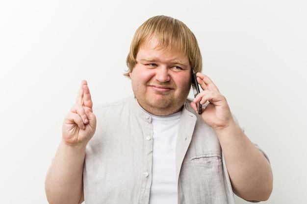 Homme de taille plus caucasien appelant par téléphone croise les doigts pour avoir de la chance Photo Premium