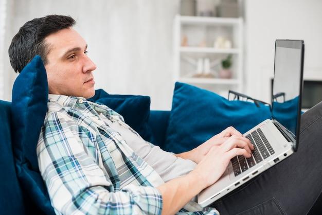 Homme taper sur un ordinateur portable et assis sur le canapé Photo gratuit