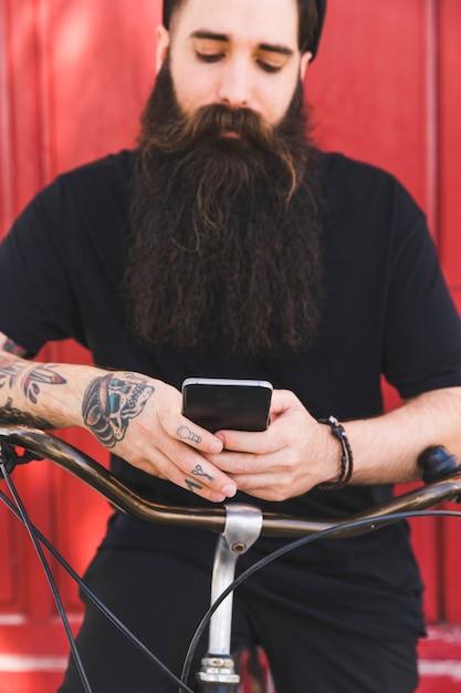Homme tatoué à l'aide d'un téléphone portable assis sur un vélo Photo gratuit