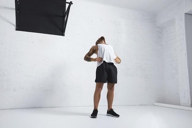 Homme Tatoué Athlétique En T-shirt Réservoir Blanc Blanc étirant Sa Poitrine Et Ses Abdominaux Après L'entraînement, Isolé Sur Un Mur De Briques, à Côté De La Barre De Traction Noire Photo gratuit