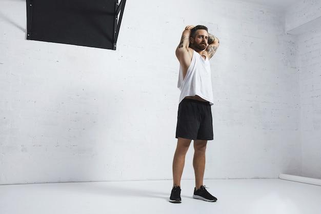 Homme Tatoué Athlétique En T-shirt Réservoir Blanc Blanc étirant Ses Triceps Sur Les Bras Après L'entraînement, Isolé Sur Le Mur De Briques Photo gratuit