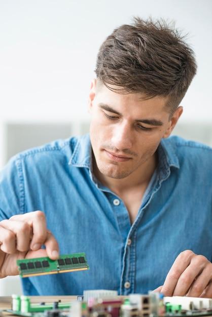 Homme technicien installant de la ram sur la carte mère de l'ordinateur Photo gratuit