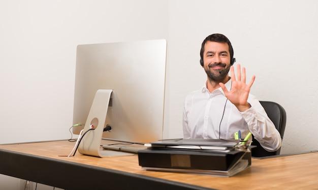 Homme de téléphone dans un bureau comptant cinq avec les doigts Photo Premium