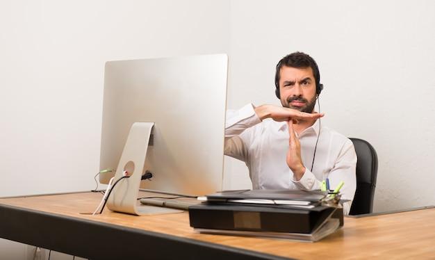 Homme télévendeur dans un bureau faisant un geste d'arrêt avec sa main pour arrêter un acte Photo Premium