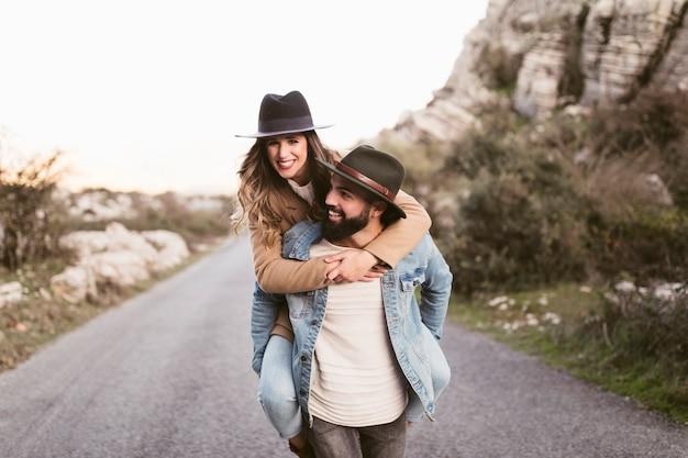 Homme Tenant Une Belle Femme Et Marchant Sur La Route Photo gratuit