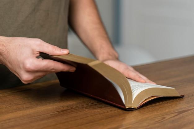 Homme Tenant La Bible Sur La Table Photo gratuit
