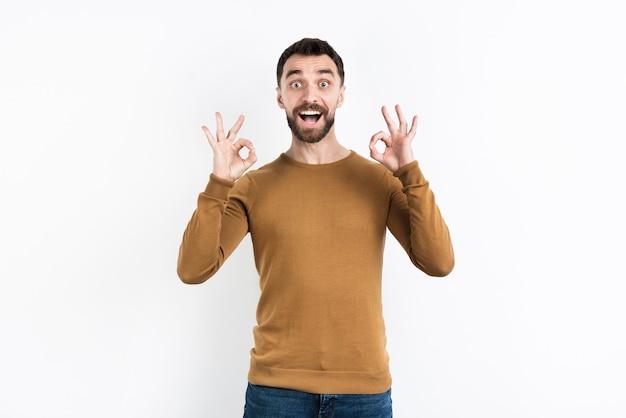 Homme tenant bien signe avec les deux mains Photo gratuit