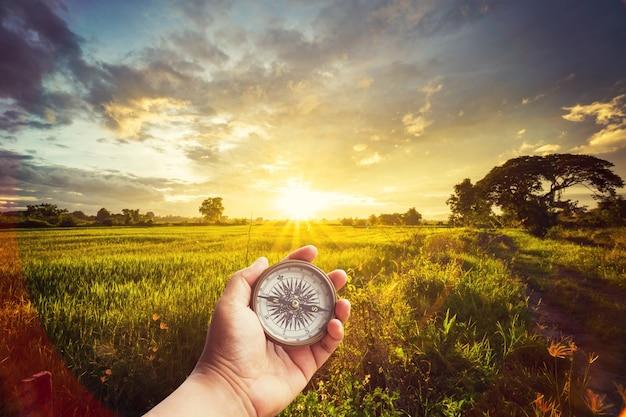 Un homme tenant la boussole à portée de main au champ et au coucher du soleil pour le guide de navigation. Photo Premium