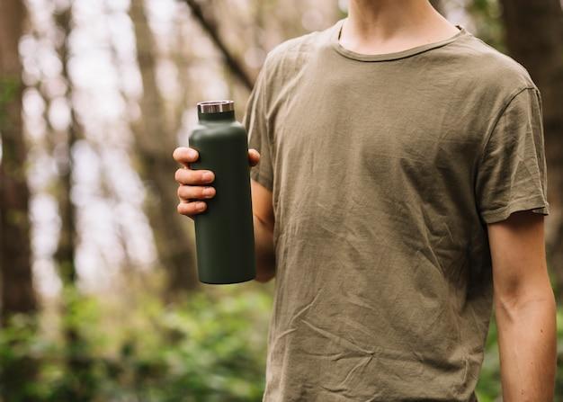 Homme tenant une bouteille d'eau dans la nature Photo gratuit
