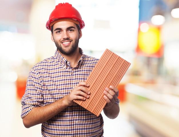 Homme Tenant Une Brique Photo gratuit
