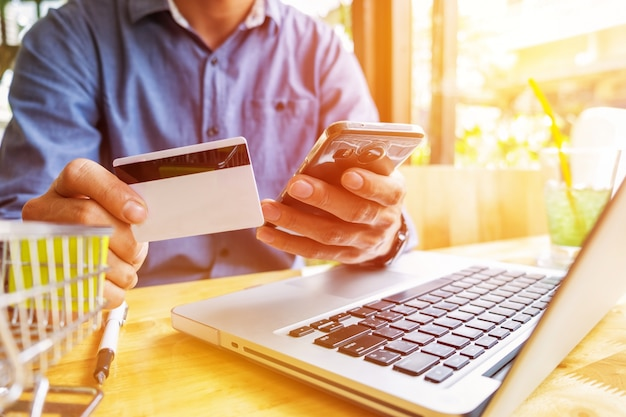 Homme Tenant La Carte De Crédit En Main Et Entrant Le Code De Sécurité à L'aide Du Clavier De L'ordinateur Portable Photo gratuit