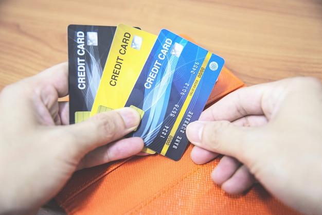 Homme tenant une carte de crédit en main - paiement en ligne à partir de la maison ou concept de carte de crédit pour dettes à accroissement Photo Premium