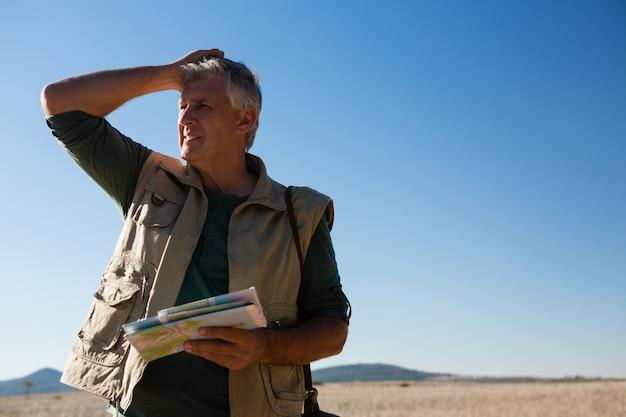 Homme tenant la carte sur le paysage Photo gratuit