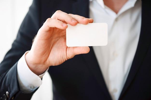 Homme tenant une carte en plastique vierge Photo gratuit