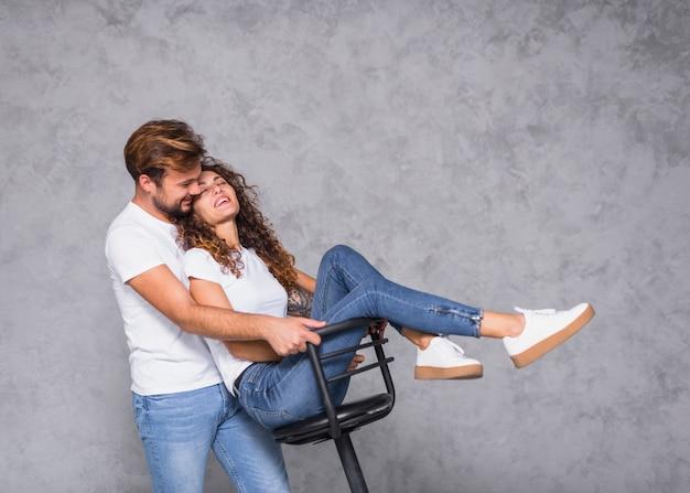 Homme tenant une chaise avec une femme Photo gratuit