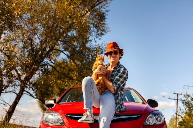 Homme tenant un chat mignon devant la voiture Photo gratuit