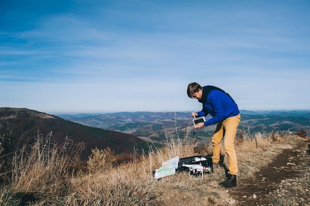 Homme Tenant Un Drone Pour La Photographie Aérienne. Silhouette Contre Le Ciel Du Coucher Du Soleil Photo Premium