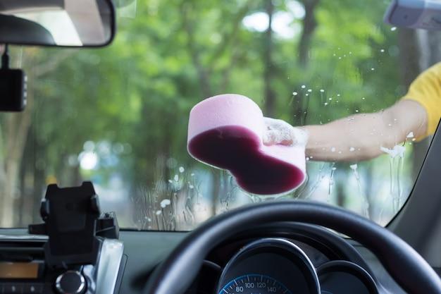 Homme tenant une éponge pour laver une voiture blanche Photo Premium
