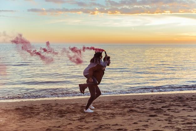 Homme tenant une femme avec une bombe de fumée rose sur le dos Photo gratuit