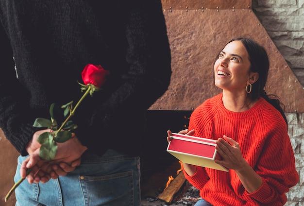 Homme tenant une fleur rose pour femme derrière le dos Photo gratuit
