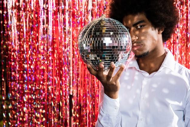 Homme tenant un fond d'espace disco ball et copie Photo gratuit