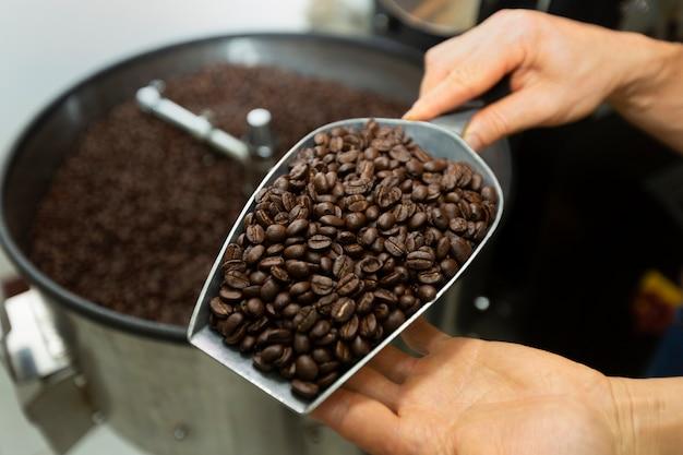 Homme tenant des grains de café à deux mains, vérifiant la qualité après torréfaction par machine moderne Photo Premium