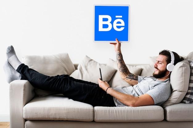 Homme tenant une icône behance sur le canapé Photo gratuit