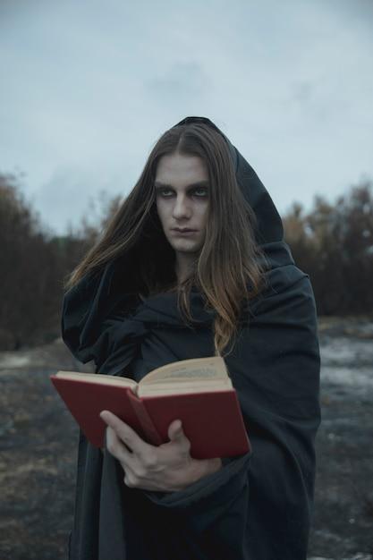 Homme tenant un livre de sorts et regardant ailleurs Photo gratuit