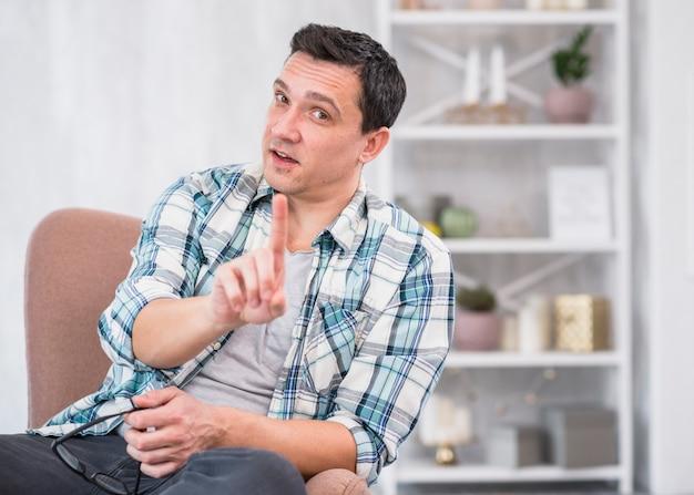 Homme tenant des lunettes et montrant l'index sur une chaise à la maison Photo gratuit