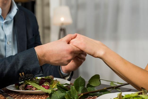 Homme, tenant main, de, femme, à, table, à, plaques Photo gratuit