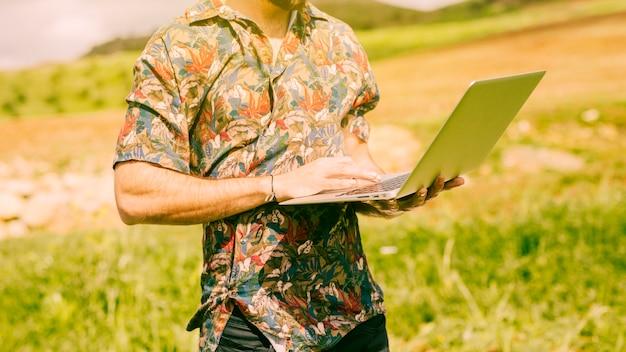 Homme tenant un ordinateur portable dans le champ Photo gratuit