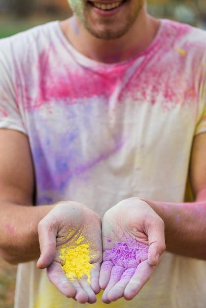Homme tenant de la peinture en poudre dans ses mains à holi Photo gratuit