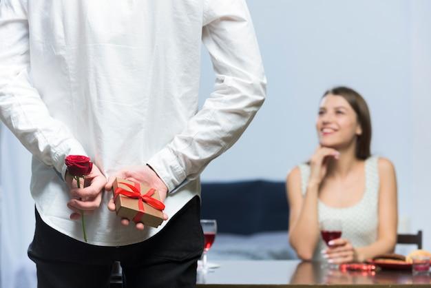 Homme tenant un petit cadeau et rose derrière le dos Photo gratuit