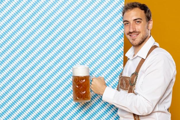 Homme tenant une pinte de bière et fond à motifs Photo gratuit