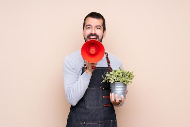 Homme tenant une plante sur fond isolé en criant à travers un mégaphone Photo Premium