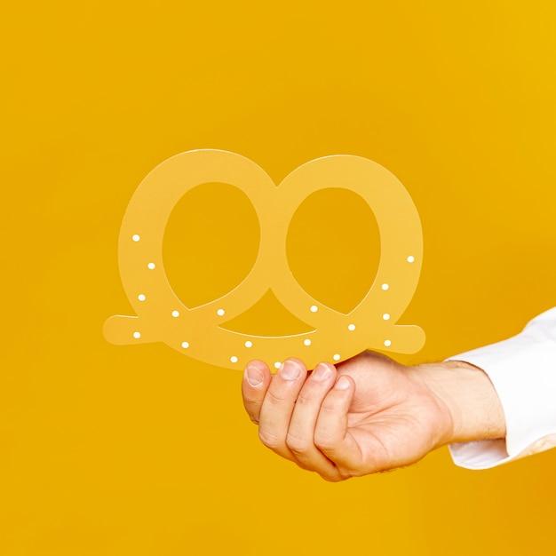 Homme tenant une réplique de bretzel allemand Photo gratuit
