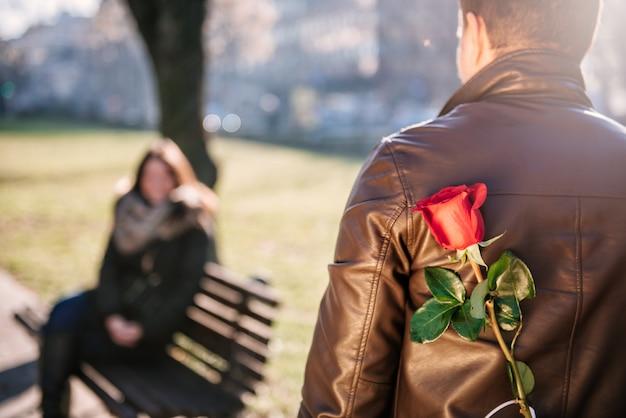 Homme tenant une rose rouge derrière le dos Photo Premium
